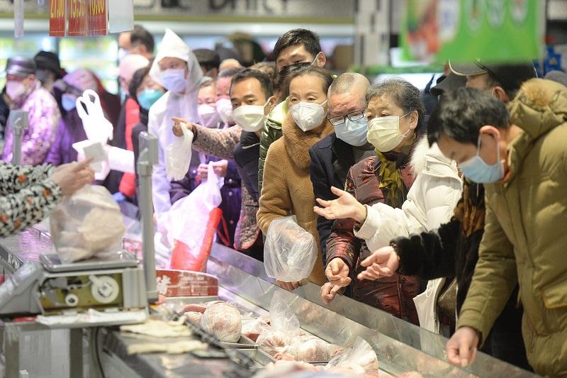 Pessoas usam máscaras para fazer compras em Wuhan | Foto: STF / AFP / CP