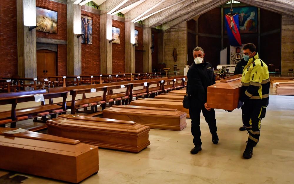 Na Itália, caixões são levados ao interior de uma igreja — Foto: Claudio Furlan/LaPresse via AP