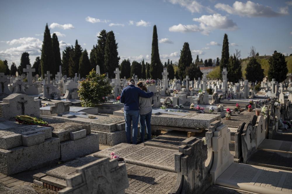Duas pessoas usam máscaras protetoras contra a Covid-19 em um cemitério durante um enterro em Madri, na Espanha, na sexta-feira (27). O país registrou 832 mortes entre a sexta e o sábado (28). — Foto: Bernat Armangue/AP