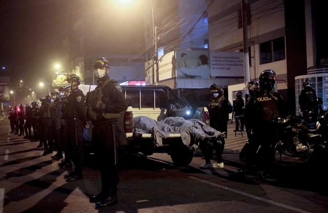Policiais colocam corpos dentro de caminhão em Lima, no Peru — Foto: AP Photo/Diego Vertiz
