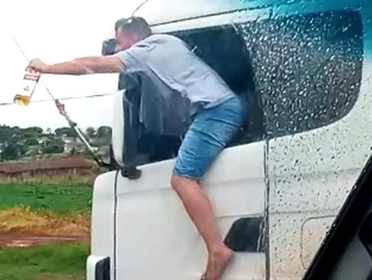 Caminhoneiro é filmado com corpo para fora de veículo com garrafa de bebida na mão enquanto dirige no Paraná — Foto: Divulgação