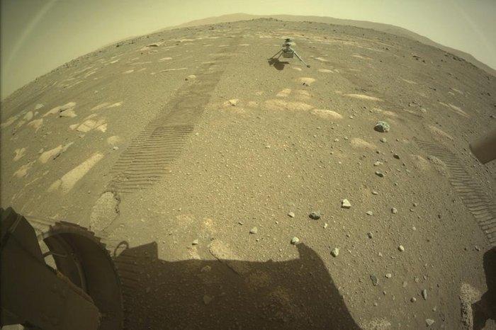 Mini-helicóptero Ingenuity Mars da NASA no solo atrás do rover Perseverance - Foto: AFP PHOTO / NASA/JPL-CALTECH